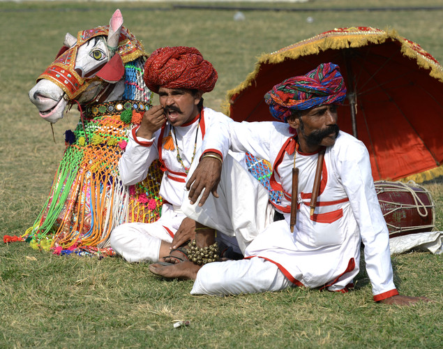 Indian artists rest during the Delhi International Kite Festival 2012 on the lawns of the India Gate monument in New Delhi.