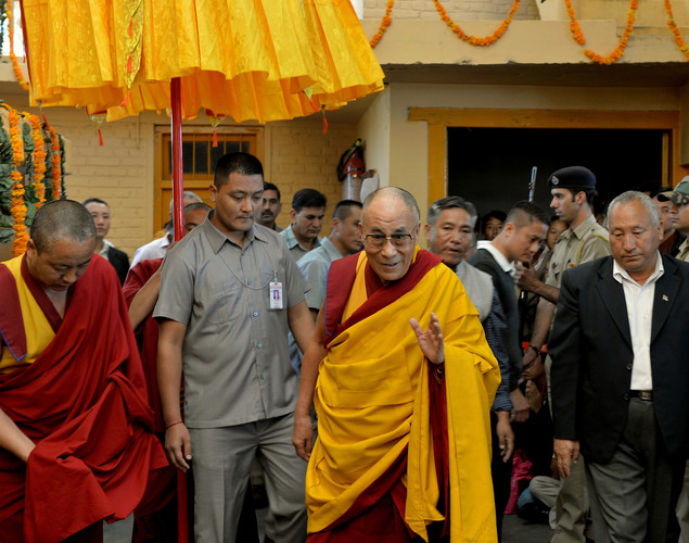 Tibetans spiritual head The Dalai Lama (C) greets Buddhist devotees as he leaves The Namgyal Monastery in Dharamshala.