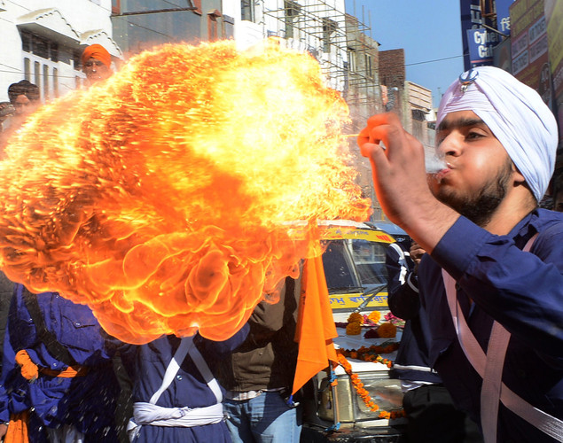 An Indian Sikh Nihang - warrior - performs a fire breathing act at a demonstration of gatka skills during a procession from Sri Akal Takhat to the Golden Temple in Amritsar on November 27, 2012 on the eve of the 543rd birth anniversary of Sri Guru Nanak Dev.