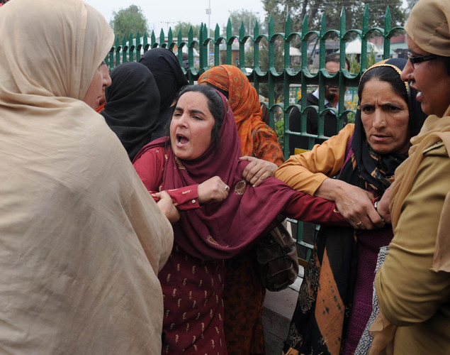 Indian police women detain a female Kashmiri government employee during a demonstration in Srinagar.