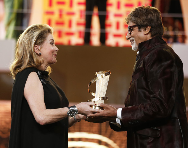 Indian film actor Amitabh Bachchan (R) receives an award from French actress Catherine Deneuve (L) during the tribute to Hindi cinema at the 12th Marrakech International Film Festival.