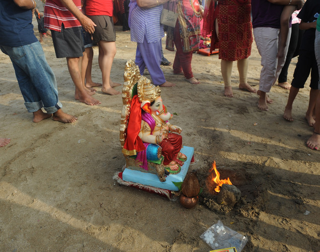 Indian Hindu devotees walk around an idol of elephant-headed Hindu god Ganesha as they chant mantras-religious hymns during a traditional ritual for immersion at the iconic Juhu Chowpatty beach on the fifth day of the ten-day long festival Ganesh Chaturthi, in Mumbai.