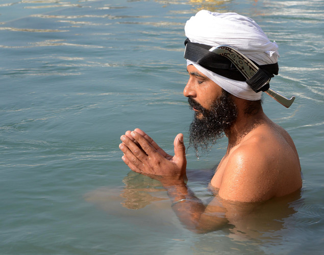 An Indian Sikh devotee takes a dip in the sarover - water tank - at the Sikh Shrine Golden Temple in Amritsar on November 27, 2012 on the eve of the 543rd birth anniversary of Sri Guru Nanak Dev.