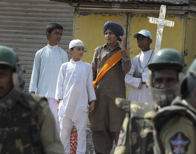 Indian children dressed in traditional Hindu, Muslim, Sikh and Christian devotees are pictured behind a police line near the barricaded Charminar monument after Friday congregational prayers in the old city section of Hyderabad.