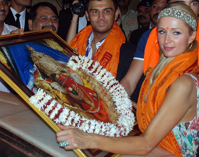 Fashion designer, socialite and DJ, Paris Whitney Hilton poses with a photograph of an idol of the Elephant Headed Hindu God, Lord Ganesha during her visit to a temple in Mumbai.