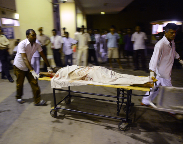 Sri Lankan hospital workers carry a victim of clashes between elite police Special Task Force and inmates on a stretcher at the main hospital in Colombo.