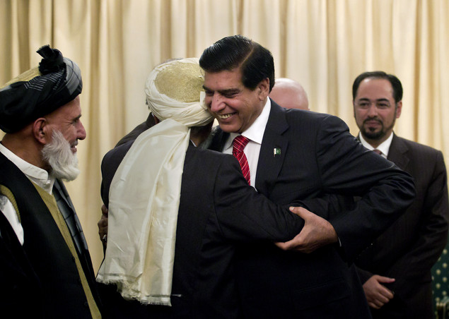 Pakistan's Prime Minister Raja Pervaiz Ashraf, center, hugs a member of the delegation of Afghanistan's High Peace Council, prior to their meeting in Islamabad, Pakistan, Monday, Nov. 12, 2012. The council's head Salahuddin Rabbani stands at right.