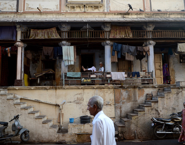 An elderly resident (background C) sits outside his residence as pedestrians walk past in the old city of Ahmedabad.