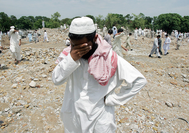 Former Pakistani students of the radical Islamic Red Mosque weep as they walk on the rubble of Jamia Hafsa, a Islamic girls seminary, in the compound of the Red Mosque demolished by the government in Islamabad, 27 July 2007.