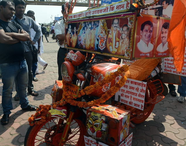 Bystanders look at a a decorated motorcycle adorned with photographs of ailing right-wing Hindu party Shiv Sena supremo Bal Thackeray near the Thackeray residence in Mumbai.