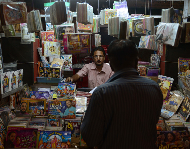 An Indian vendor sells music CDs at a roadside shop in the walled city of Ahmedabad.