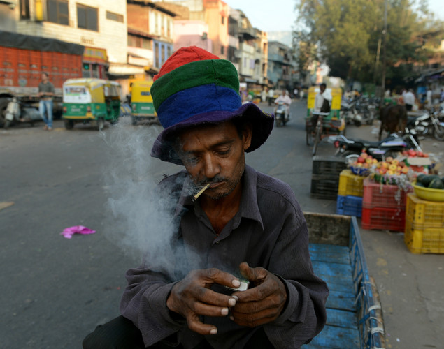 A laborer lights a bidi (leaf cigarette) as he sits on his cycle carrier in the old city of Ahmedabad.