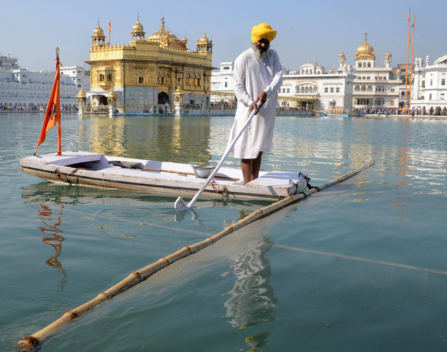 An Indian Sikh devotee cleans the sarover - water tank - at The Sikh Shrine Golden Temple in Amritsar on November 27, 2012 on the eve of the 543rd birth anniversary of Sri Guru Nanak Dev.