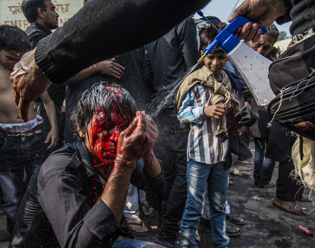 A Shiite Muslim man has water sprayed onto him after having cut himself as part of a self-flagellation ritual during a religious procession marking Ashura.