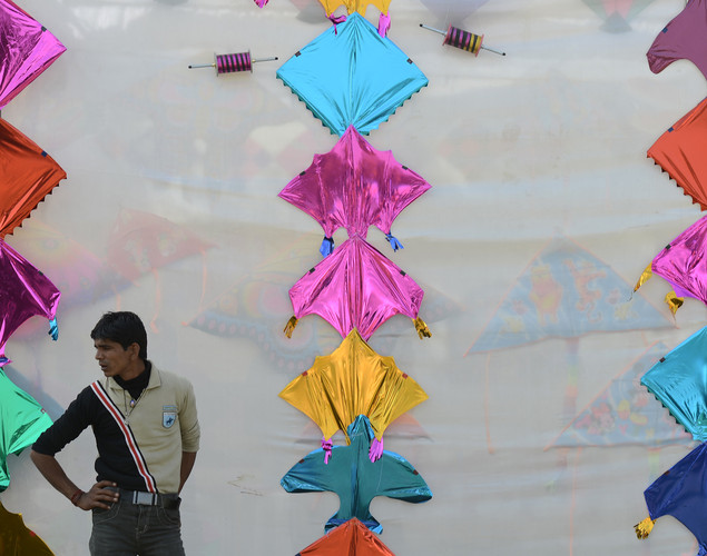 An Indian tea vendor stands in front a display during the Delhi International Kite Festival 2012 on the lawns of the India Gate monument in New Delhi.