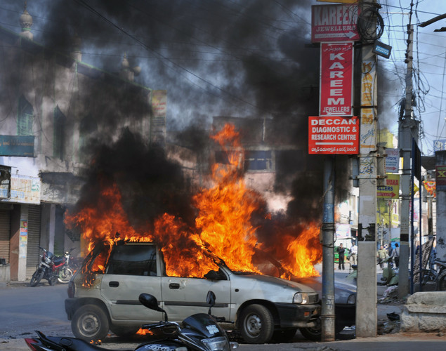 Flames and smoke rise from burning cars following violence after Friday congregational prayers in the old city section of Hyderabad.