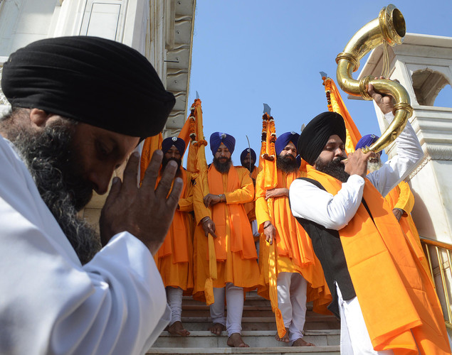 An Indian Sikh devotee plays a musical instrument as he walks with Punj Pyara holding flags of the Sikh religion as they escort a procession from Sri Akal Takhat at The Golden Temple in Amritsar on November 27, 2012 on the eve of the 543rd birth anniversary of Sri Guru Nanak Dev.