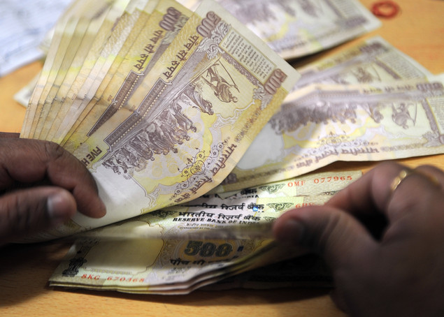 A bank cashier counts Indian Rupee notes at a bank in Mumbai.