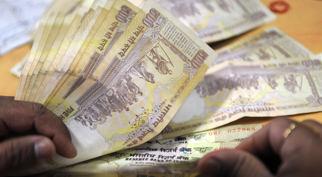 A bank cashier counts Indian Rupee notes at a bank in Mumbai.