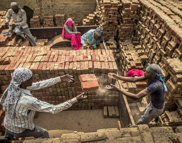 Laborers pass baked bricks at a brick making facility on May 23, 2012 in a village near Jaipur, India.