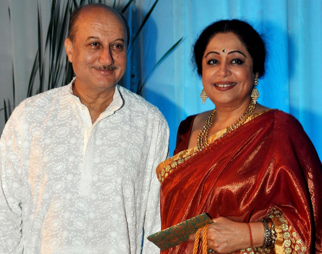 Bollywood film actress Kirron Kher (R) and her husband Anupam Kher pose during the wedding reception of film actress Esha Deol and husband Bharat Takhtani in Mumbai.