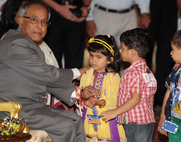 An Indian girl ties a 'Rakhi' - Sacred Thread - onto the wrist of Indian President Pranab Mukherjee (L) at The Presidential Palace in New Delhi.
