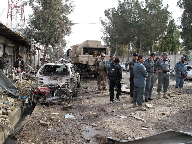 Afghan policemen investigates the scene of a suicide attack in Lashkar Gah Helmand province on January 26, 2012.