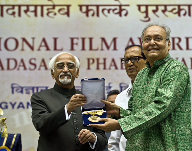 Indian Vice President Hamid Ansari (L) presents the Dada Saheb Phalke award to Soumitra Chatterjee (R) during the 59th National Film Award in New Delhi.