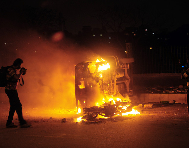 A Pakistani news photographer shoots a burning police van during a protest rally organized by Pakistani Shiite Muslims against an American produced film mocking Islam on September 16, 2012 in Karachi.