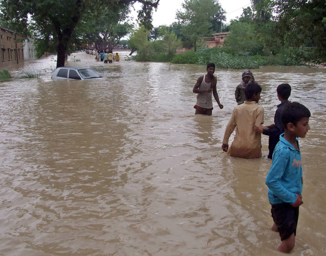 Pakistani people wade through a flooded area caused by heavy monsoon rains.