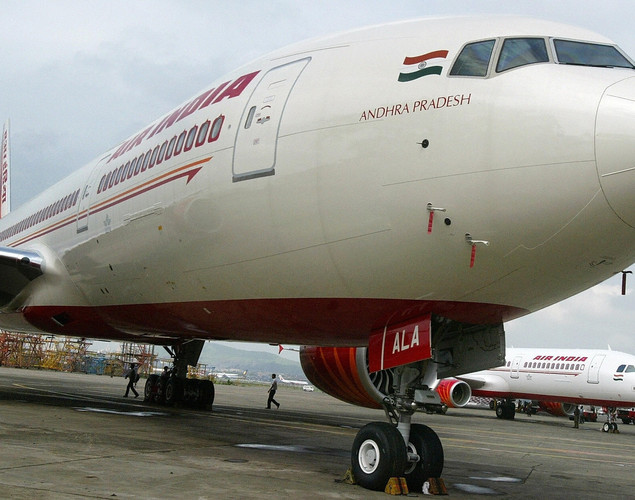 Indian security personnel walk past Air India's newly acquired Boeing 777-200 LR aircraft