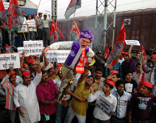 Activists from India's Samajwadi Party shout slogans as they hold a burning effigy of Indian Prime Minister Manmohan Singh while halting the progress of an express train in Allahabad.
