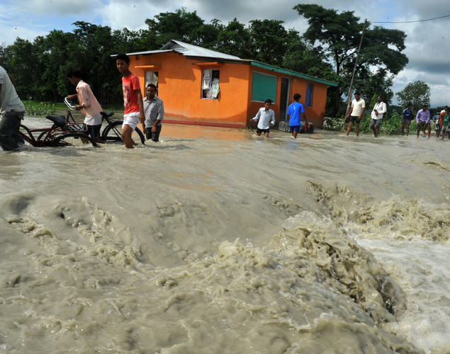 Indian residents wade through the flood waters at Milanmore village on the outskirts of Siliguri.