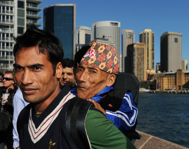 Chandra Bahadur Dangi (R), the 72-year-old Nepali crowned the 'world's shortest man' by Guinness World Records, is carried by his nephew Dolakh Dangi (L), following a press conference at Circular Quay on Sydney Harbor at the start of a week of promotional engagements.