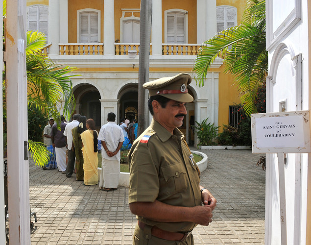 An Indian security guard stands outside a polling booth while Indo-French citizens stand in line to cast their votes in Pondicherry on April 22, 2012, during the first round of French presidential elections.