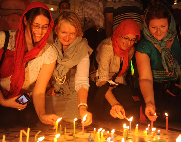 Foreign tourists light candles at the illuminated Golden Temple in Amritsar .