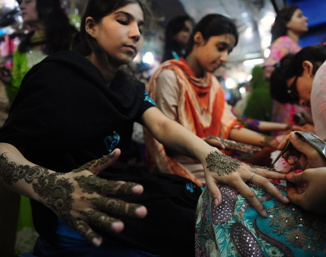 Pakistani beauticians apply traditional henna designs to the hands of customers ahead of the Muslim festivities of Eid al-Fitr, in Karachi.