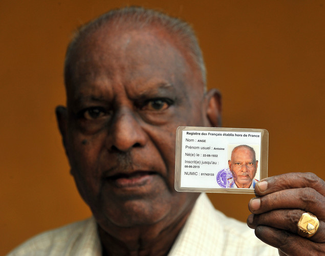 An elderly Indo-French citizen shows his French registration card outside a polling booth in Pondicherry on April 22, 2012, prior to casting his vote during the first round of French presidential elections.