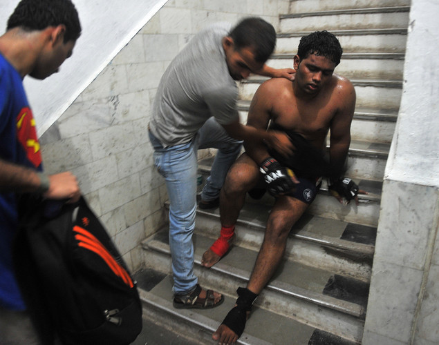Indian student, judo practitioner and mixed martial arts (MMA) fighter Aditya Despande (L) and his opponent Tanaji Patil help fellow fighter Nitin Gaikwad after he collapsed from exhaustion during the FCC (Full Contact Championship) 6 fight night in Mumbai.