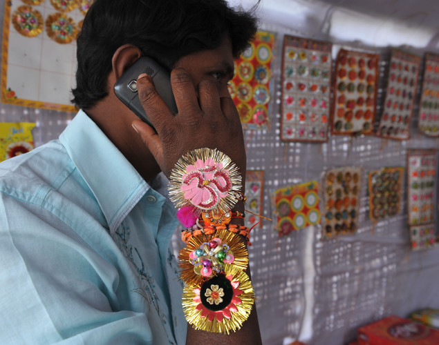 An Indian man talks on his mobile phone with 'rakhi' - sacred threads - on his wrist in Hyderabad.