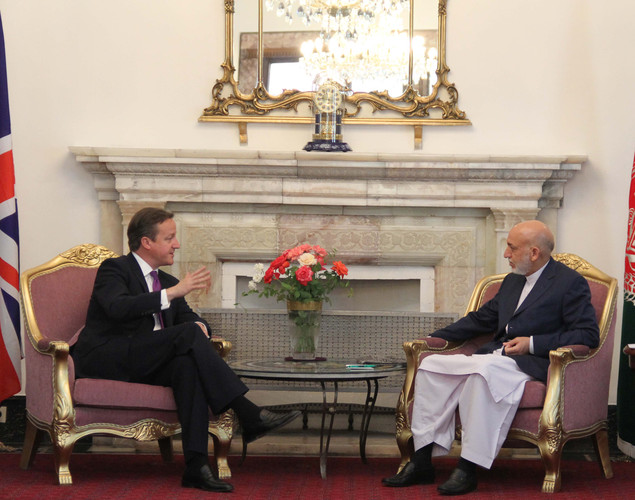 Afghan President Hamid Karzai (R) speaks with Britain's Prime Minister David Cameron during a meeting in Kabul.