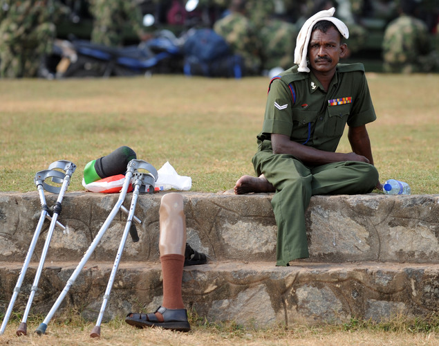 A disabled Sri Lankan Army person rests during a Victory Day parade rehearsal in Colombo.