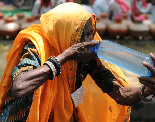 A woman drinks water on a hot summer day in New Delhi.