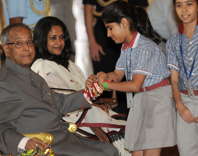 An Indian visually girl ties a 'Rakhi' - Sacred Thread - onto the wrist of Indian President Pranab Mukherjee (L) at The Presidential Palace in New Delhi.