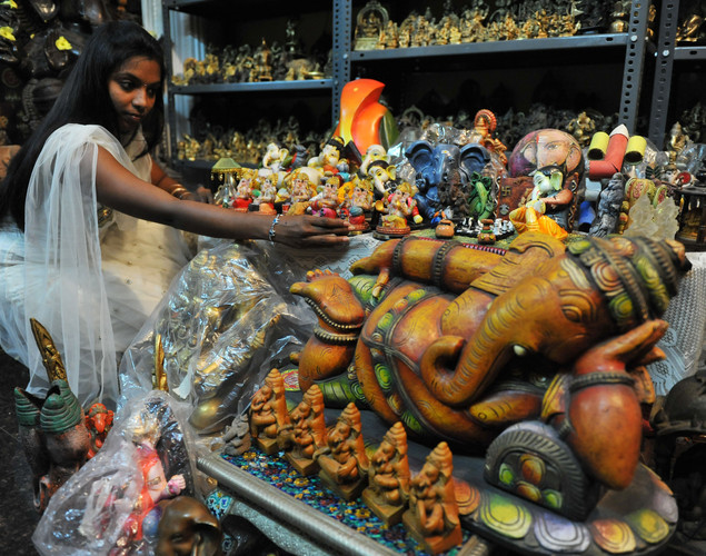 P.Sanjana daughter of Indian collector Pabsetti Shekhar holds an idol of elephant-headed Hindu god Lord Ganesh in their home collection in Hyderabad on September 18, 2012, during the festival 'Ganesh Chaturthi'.