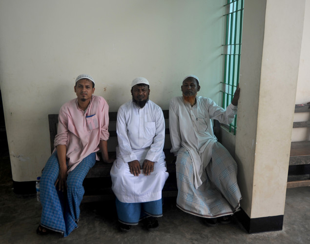Myanmar businessmen, stranded in Bangladesh following religious violence in neighbouring Myanmar, look on at the immigration office in Taknaf.