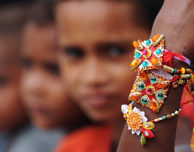 An Indian street child looks at his rakhi tied to his wrist by a member of a voluntary organization in Kolkata.