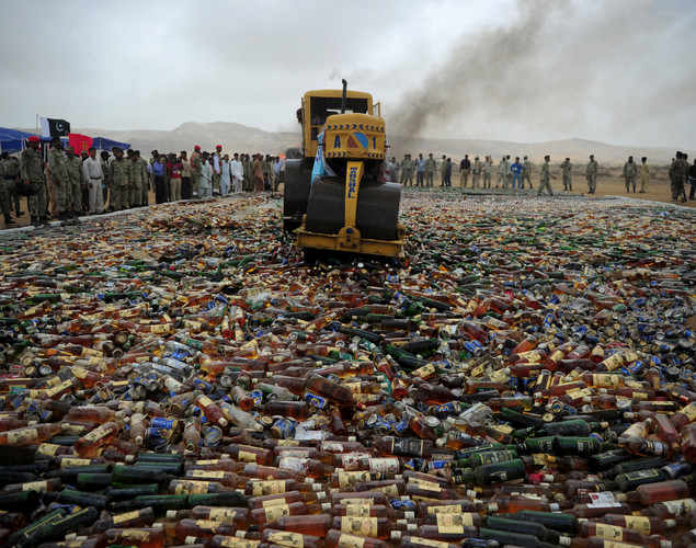 A Pakistani official uses a steamroller to crush bottles of liquor during a ceremony to mark International Day against Drug Abuse and Illicit Trafficking, in Karachi .