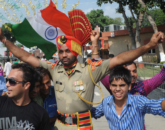 Indian revellers and an Indian Border Security Force (BSF) soldier dance and wave national flags during a ceremony to celebrate India's Independence Day at the India-Pakistan Wagah border post on August 15, 2012.