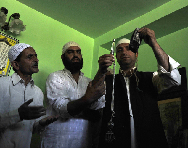 Syed Khalid Hussain (R), chief custodian of the 200-year old shrine of Sheikh Abdul Qadir Jeelani - also known as Dastigheer Sahib - which was engulfed in flames on June 25, displays a rescued relic containing the beard hair of Sheikh Abdul Qadir Jeelani, in Srinagar.